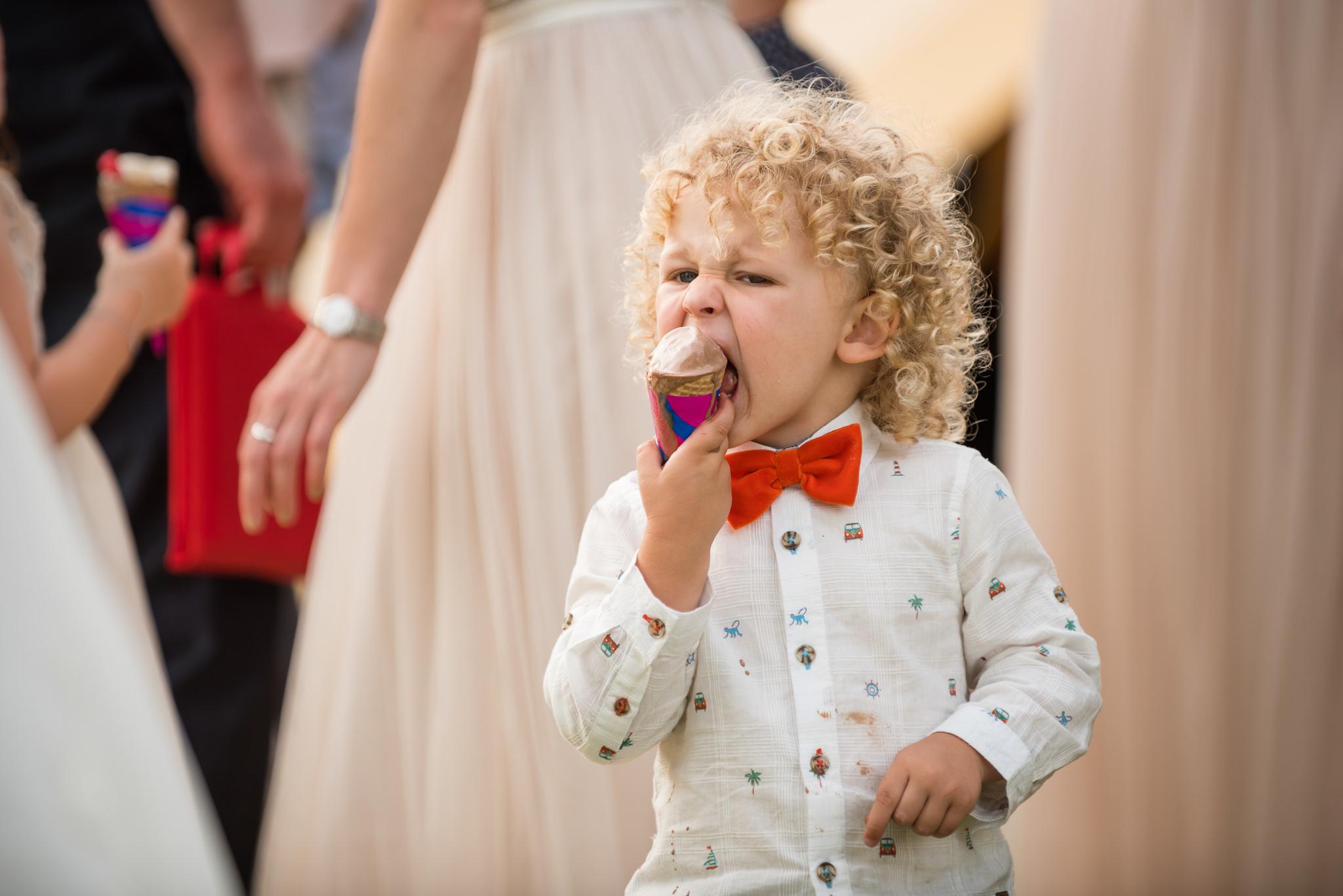 A young boy eats an ice cream dream tipi wedding reception