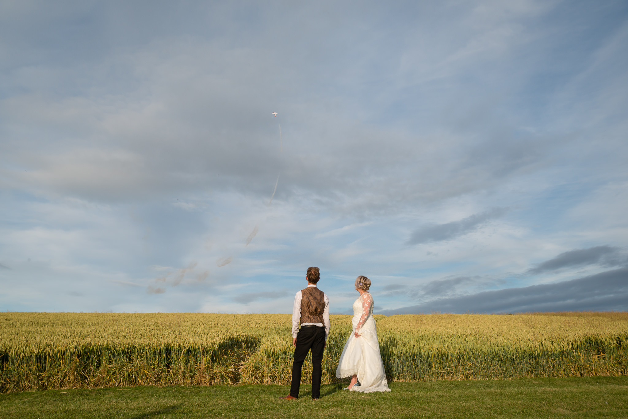 The bride and groom watch as a stunt plane flies in the sky above them