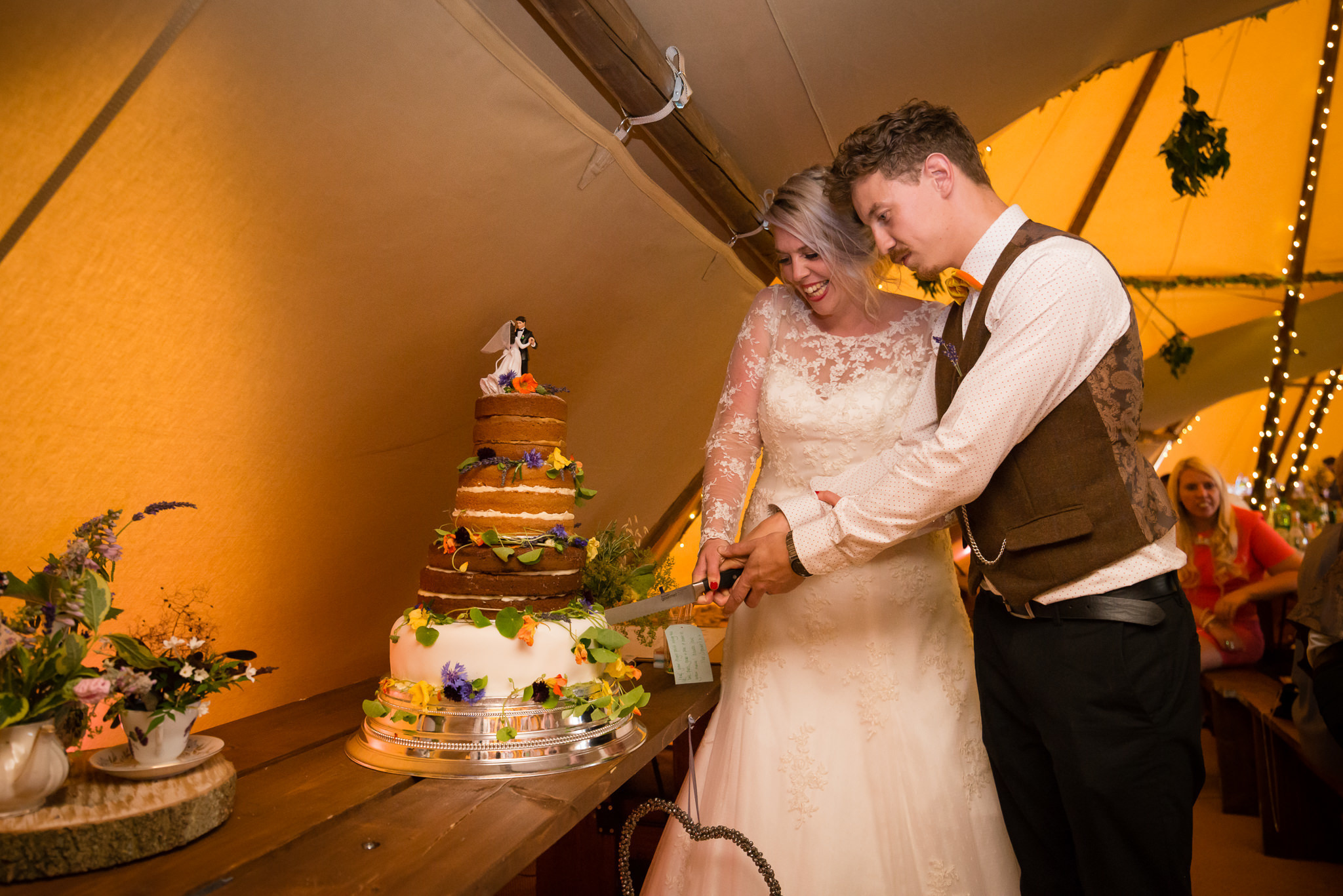 The bride and groom cut the wedding cake in the tipi