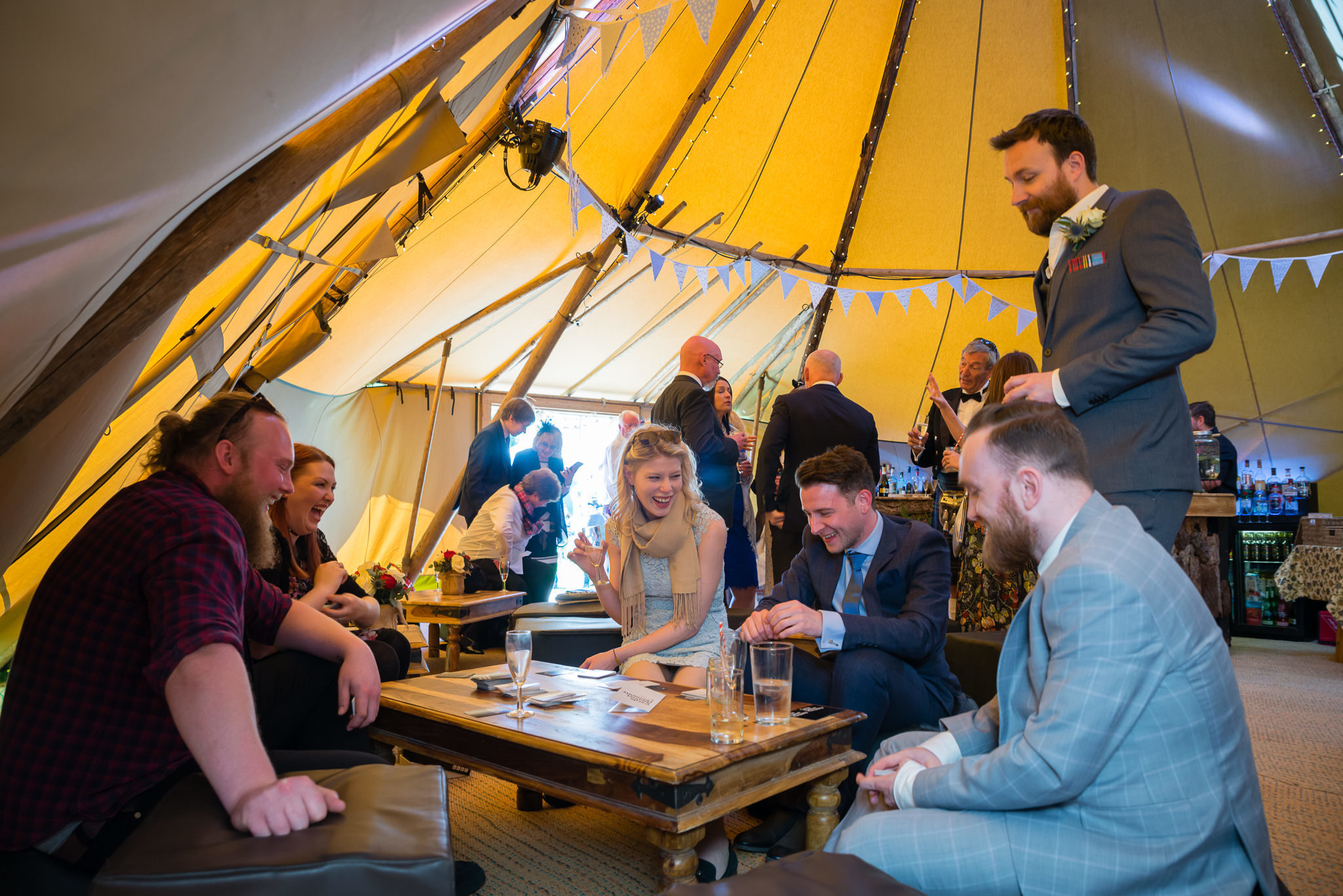 Wedding guests sitting down inside the teepee