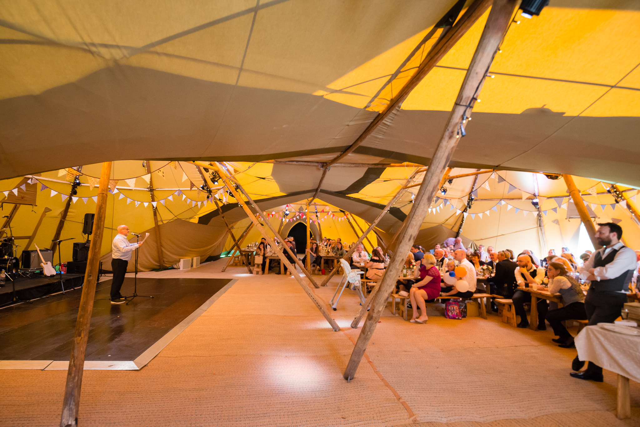 The father of the bride gives his speech in the tipi
