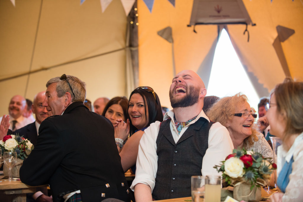 The groom laughing during a speech