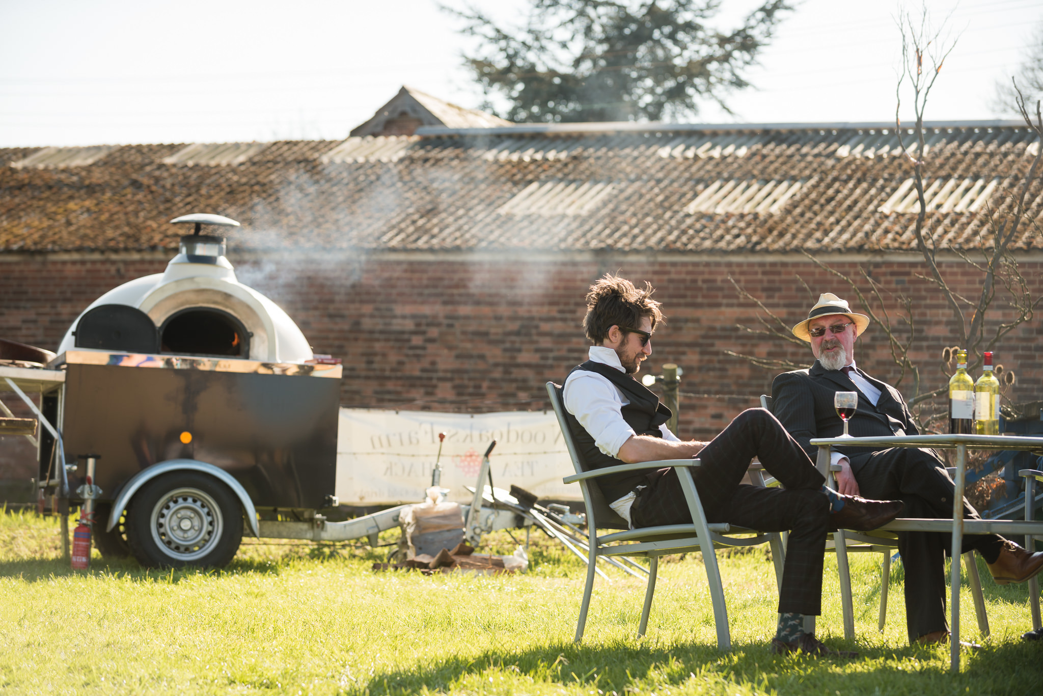Guests sitting enjoying a sunny afternoon at the tipi wedding
