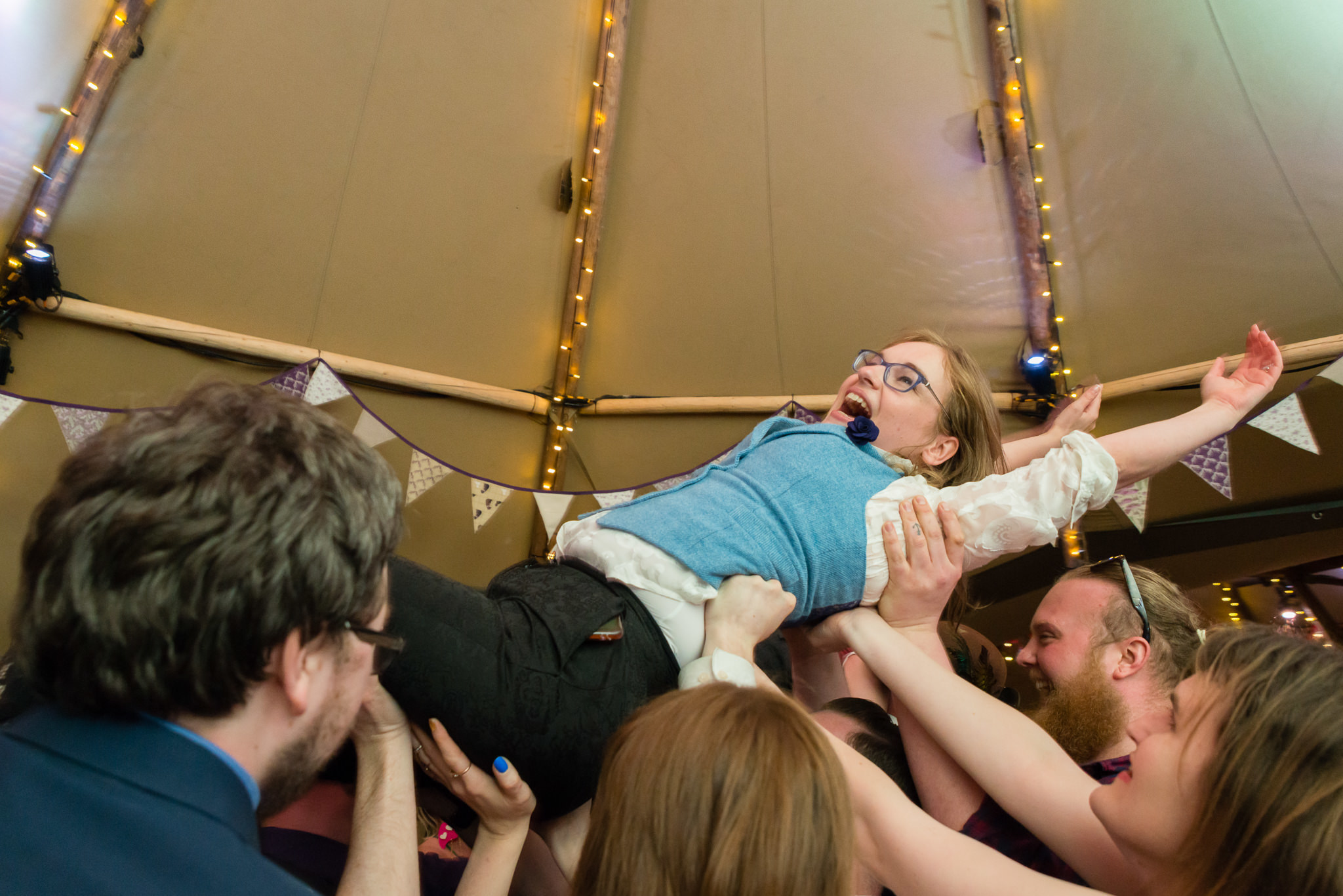 The Bride crowd Surfs during her tipi wedding reception