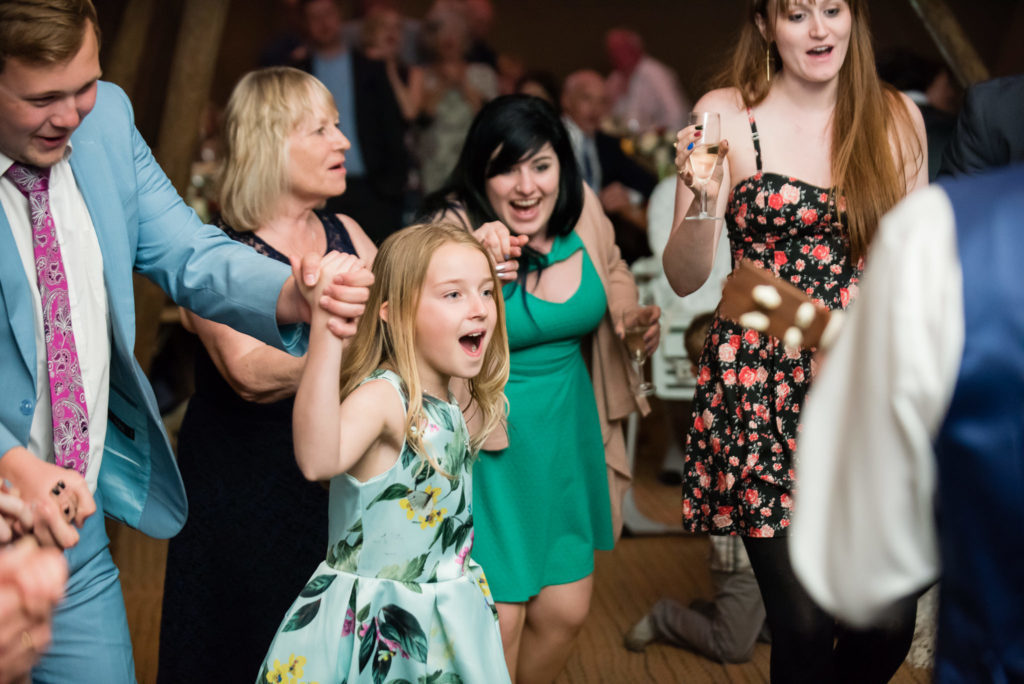 Guests dance to the hokey cokey during the tipi wedding reception