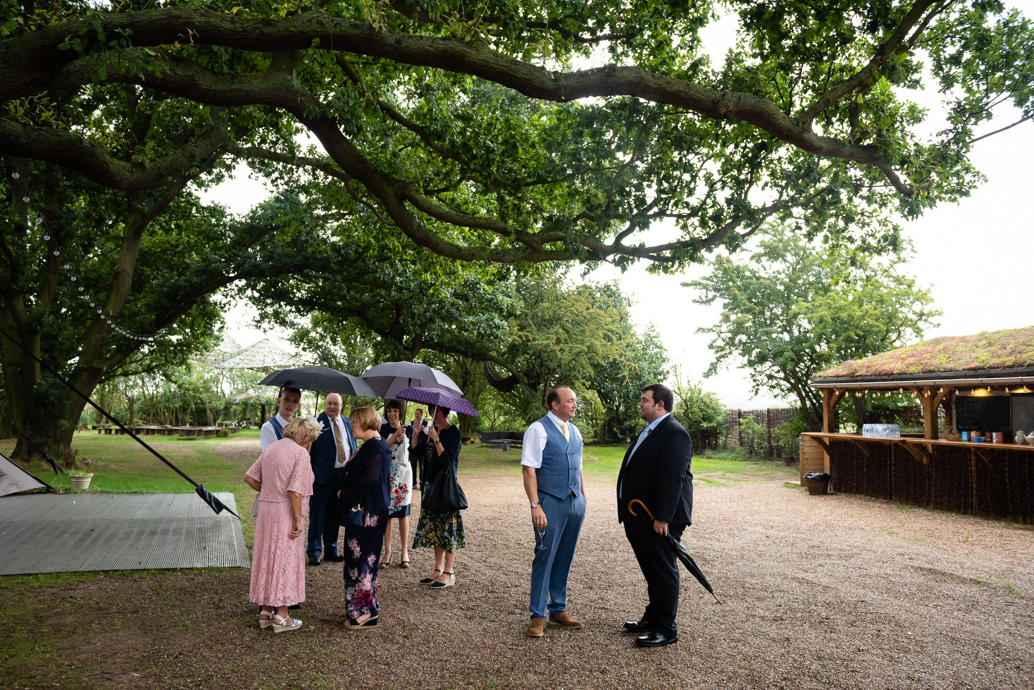 The groom greet wedding guests as they arrive at the Oak Grove