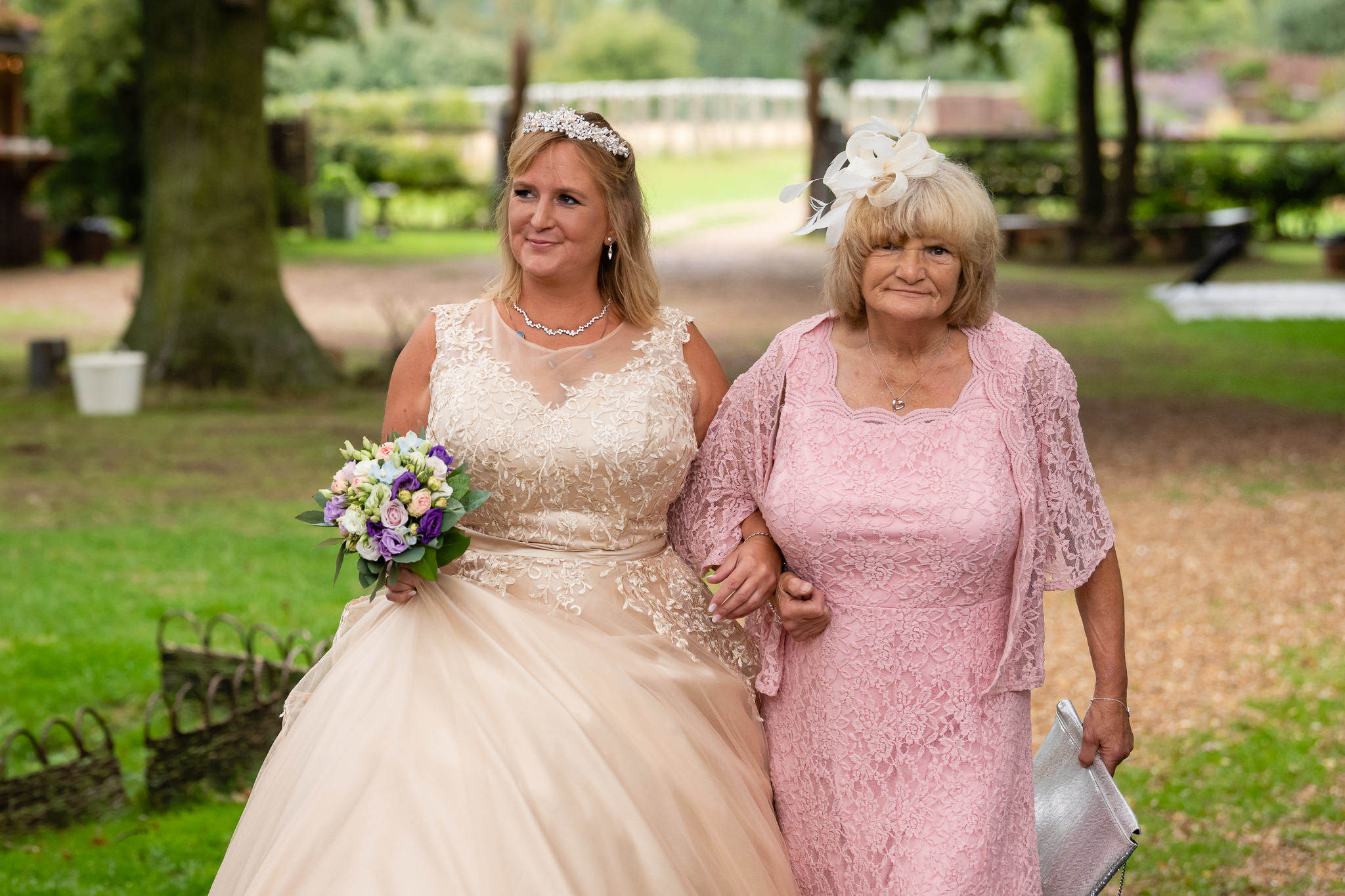 The bride and her mum walking towards the wedding ceremony