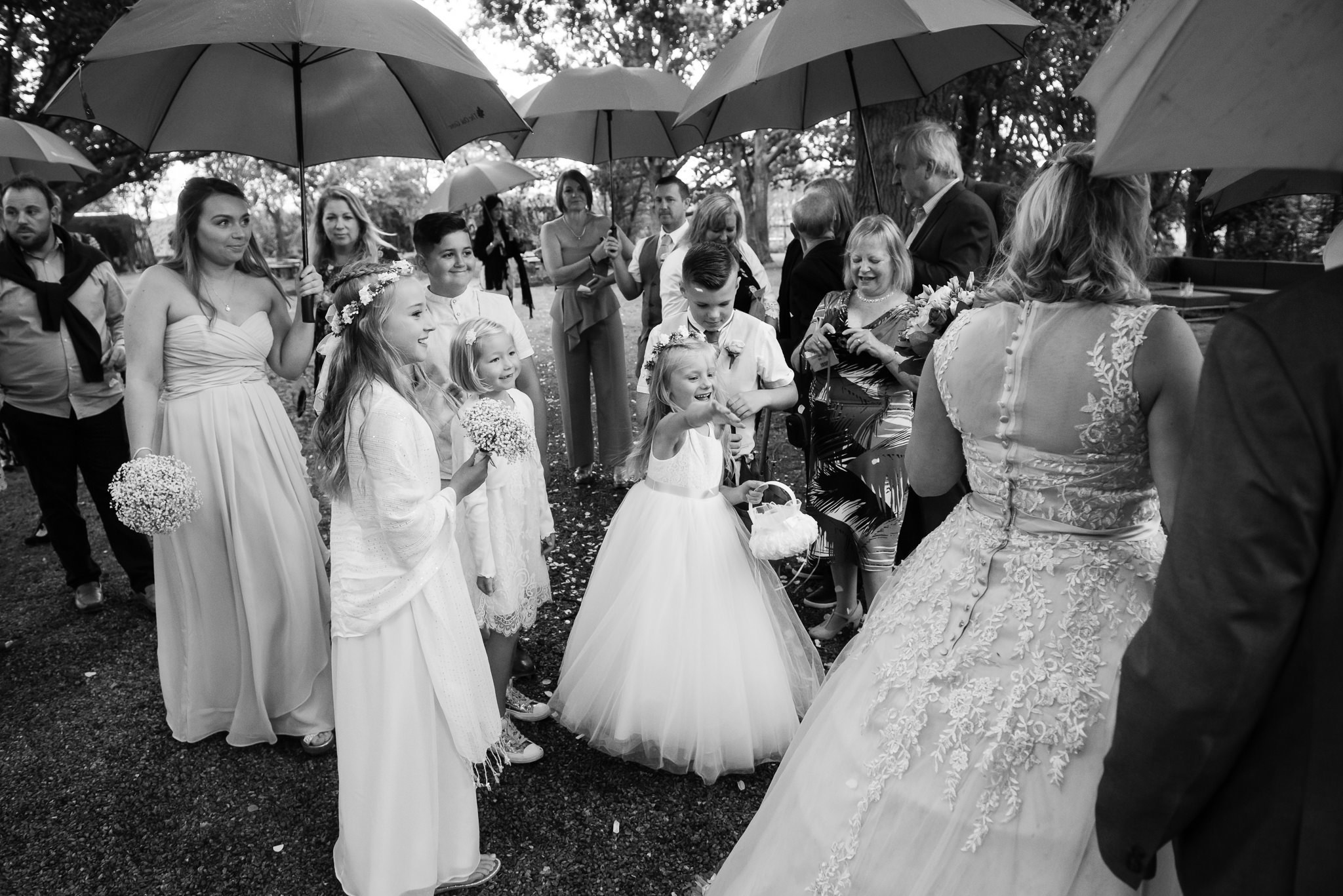A flower girl throwing confetti over the bride and groom