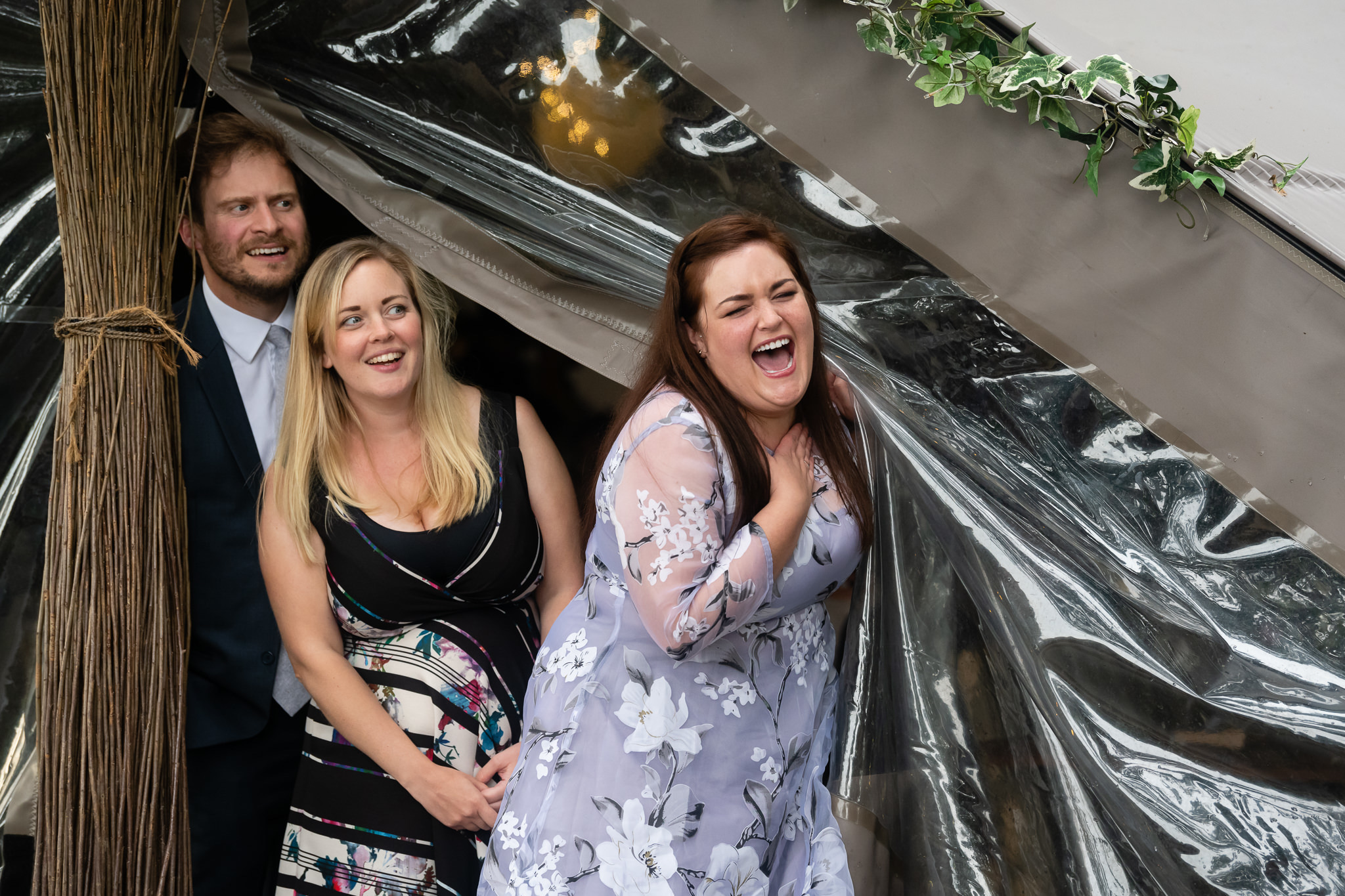 Guests laughing as they exit the stretched tent