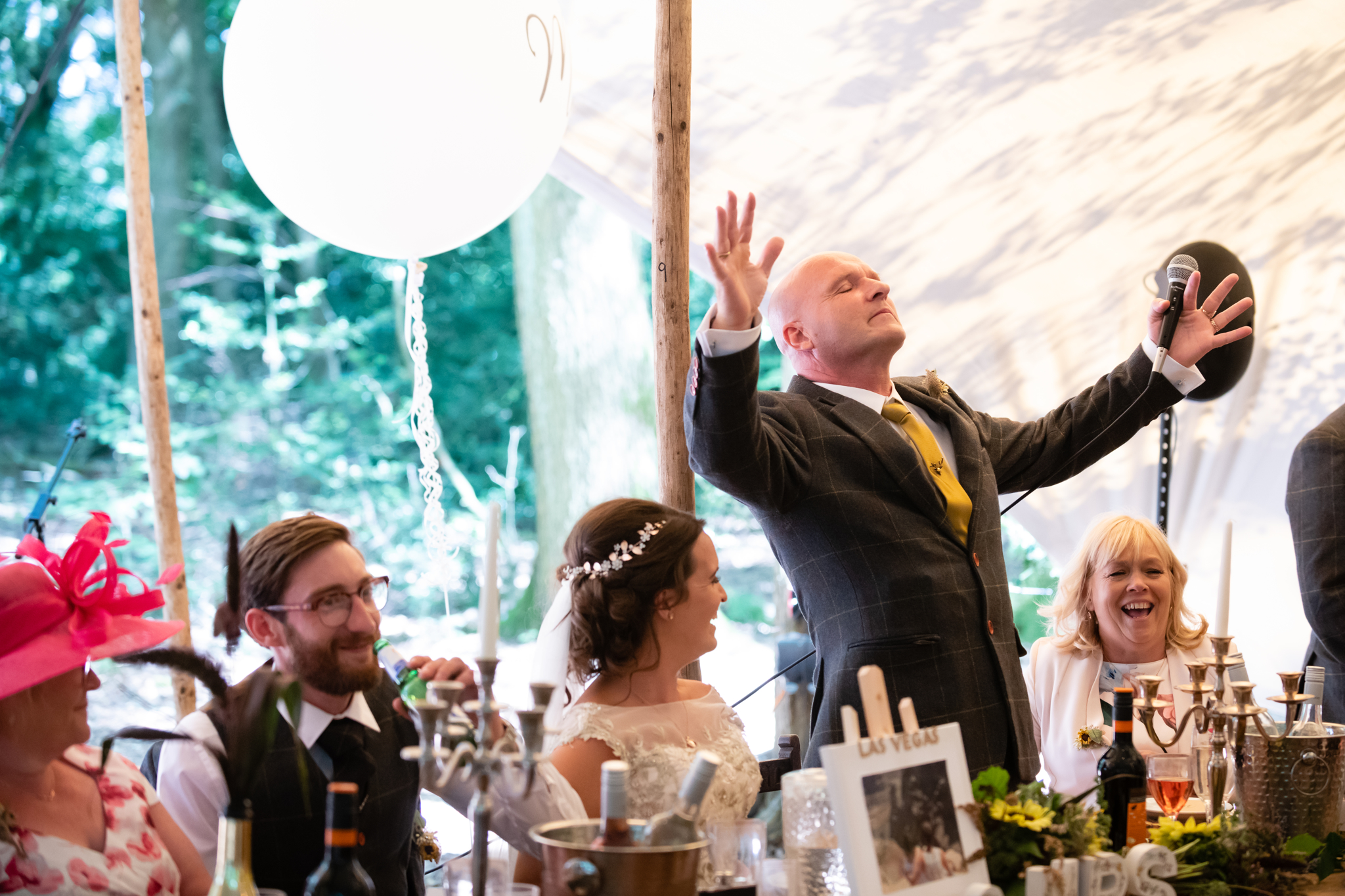 The father of the bride controlling the wedding guests cheers