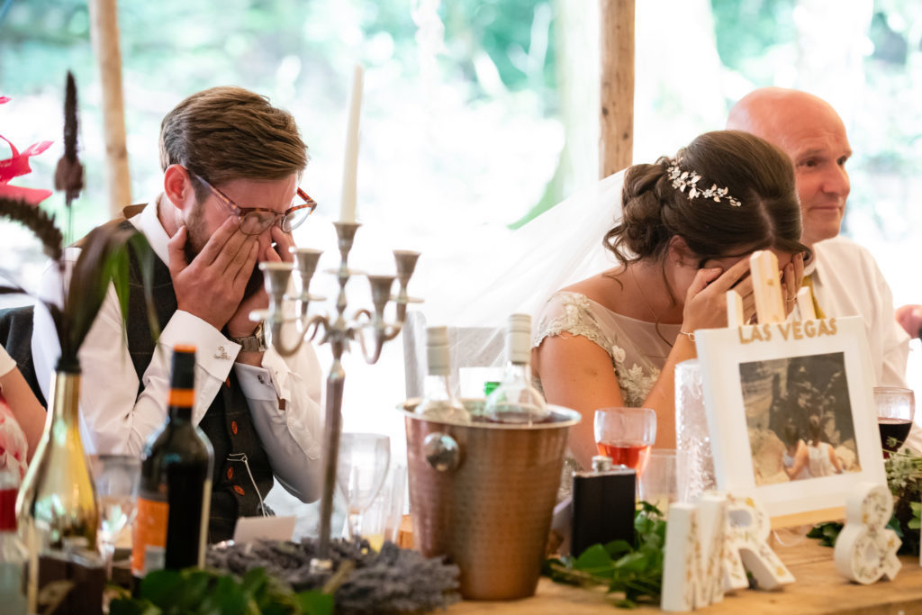 The bride and groom cringe in embarrassment during the best man speech