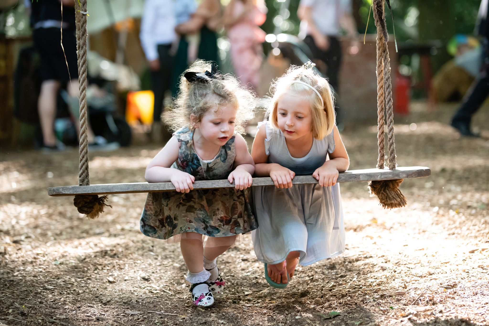 Two girls play on the swing at woodland Weddings